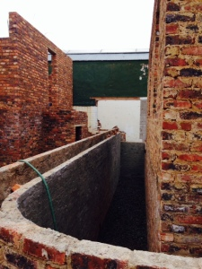 Part of this space - between the cottage and the double retaining walls - will be made into a garden storeroom.