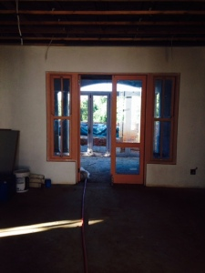 Taken from library sliding door opening, looking north, through living area and patio to garden.