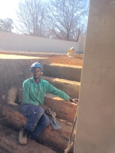 Godfrey, a bricklayer, working on the steps from the garden to the path.
